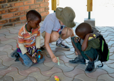 children drawing with chalk on flagstones